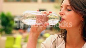 Happy student drinking water in canteen