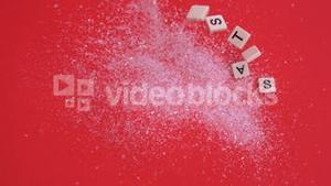 White letter tiles moving to spell out christmas on glitter on red background