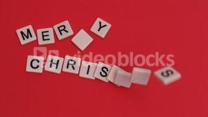 Letter tiles moving to spell out merry christmas on red background