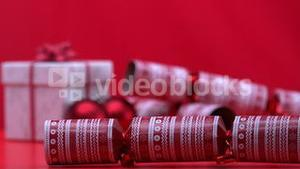 Christmas cracker spinning and bouncing beside present and bauble