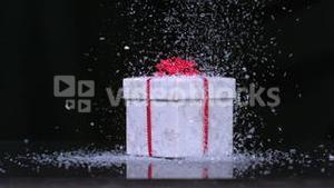 Glitter falling onto christmas present in slow motion