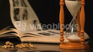 Pages turning in the wind beside hourglass and gold nuggets
