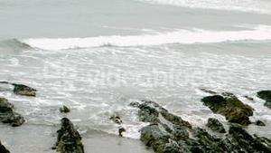 Waves rolling in on the beach over rocks