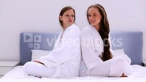 Girls wearing bathrobes chatting on bed