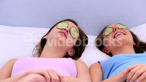 Girls lying on bed with cucumber over their eyes