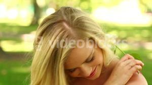 Pretty blonde relaxing in the park smiling at the camera while smelling a flower