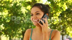 Gorgeous brunette making a call in the park