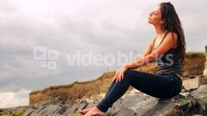 Beautiful brunette sitting on the rocks by the beach