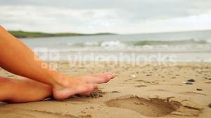 Womans legs sitting on the beach