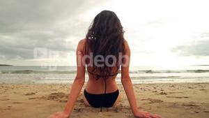 Brunette sitting on the beach facing the water