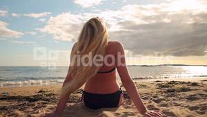 Blonde in bikini sitting on the beach facing the water