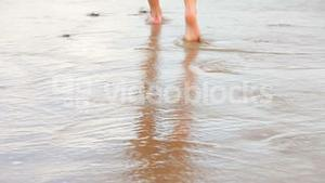 Womans feet walking on the wet sand along the tide