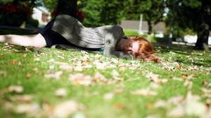 Peaceful napping redhead lying on green lawn