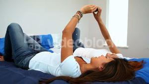Attractive happy sisters lying on bed holding smartphone