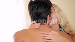 Couple sitting on bed kissing
