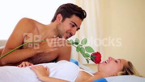 Man tickling his girlfriend with a red rose on bed