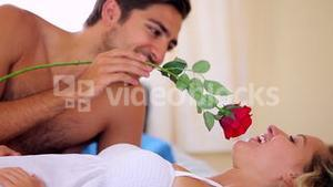 Man tickling his pretty girlfriend with a red rose on bed