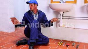 Handsome plumber fixing sink and checking tablet pc