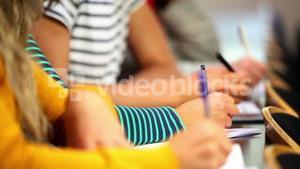 Row of students taking notes in class