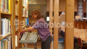Librarian pushing trolley through the library returning books