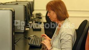 Mature student working with a computer sitting in computer room