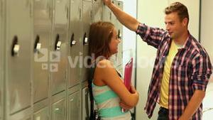 Two cute students flirting in the hallway beside lockers