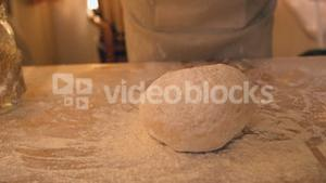 Hands dropping ball of dough onto floury surface
