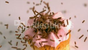 Chocolate sprinkles falling onto pink frosted cupcake