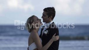 Cute newlywed couple embracing at the beach