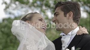 Groom kissing his pretty new wife in a park