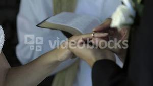 Groom placing ring on brides finger in front of priest