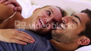 Cute couple chatting and cuddling in bed