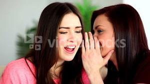 Brunette whispering secret to her shocked friend on the couch