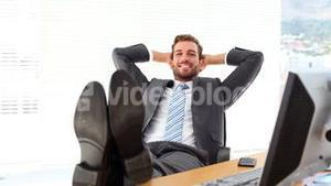 Relaxed businessman putting his feet up smiling at camera