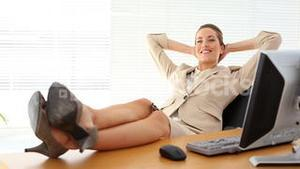 Relaxed businesswoman putting her feet up smiling at camera