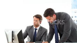 Businessmen looking at computer screen talking