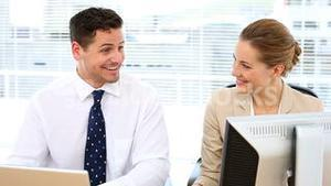 Happy business team looking at computer screen together and talking at desk