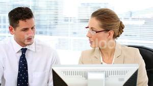 Focused business team looking at computer screen together