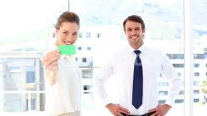 Businessman giving card to businesswoman who shows it to camera