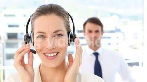 Call centre agent speaking with colleague behind her