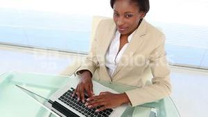 Busy businesswoman using laptop at desk