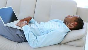 Businessman falling asleep on the couch with laptop