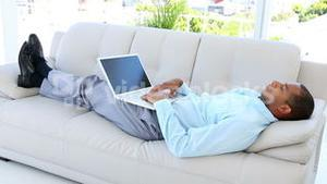 Businessman falling asleep on the sofa with laptop