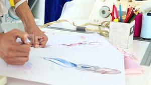 Fashion designer sketching a blue dress design