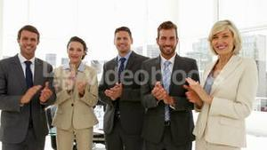 Business people clapping at the camera