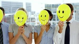 Business team holding smiley face balloons