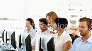 Supervisor checking on call centre workers