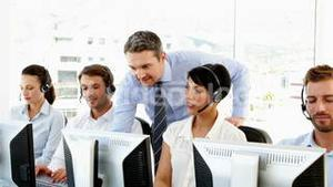 Manager checking on call centre workers