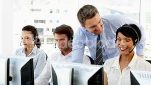 Manager checking on call centre employees