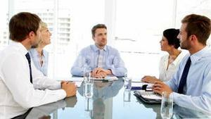 Business people listening to manager during meeting